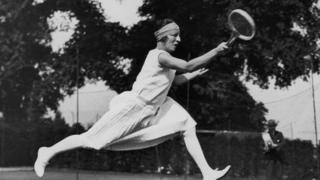 French tennis player Suzanne Lenglen wears a knee-length dress and a bandeau as she takes part in a competition in 1926.