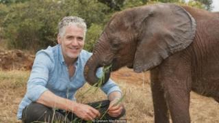 Gordon Buchanan dengan bayi gajah, David Sheldrick Wildlife Trust, Kenya.