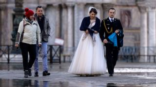 A newlywed couple walks across a flooded square in Venice, 14 November 2019