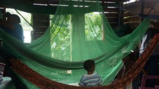 Mosquiteiro é preso em cima de rede em casa ribeirinha na Amazônia