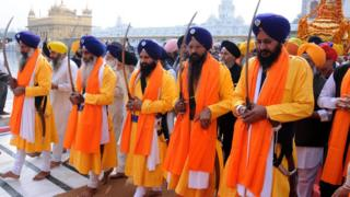 Five Beloved Ones, wearing orange robes and purple turbans and holding swords, lead a procession through the Golden Temple in Amritsar, India
