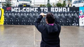 A woman takes a picture of Luke Cornish's mural on Bondi Beach in Sydney