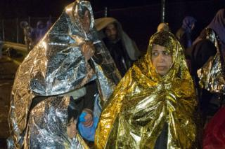 Migrants wait to cross into Slovenia, at a border crossing with Croatia, in Sredisce ob Dravi, early Monday, 19 Oct 2015