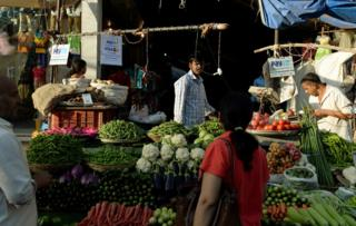 A sign advertising Indian mobile payments from Paytm hangs at vegetable stalls in Mumbai.