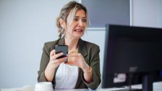 Mujer duda con el teléfono y frente a la computadora.