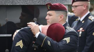 Members of Sgt La David Johnson's unit comfort each other as they attend the burial service for US Army sergeant in Hollywood, Florida, 21 October