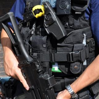 Armed British Police officer, with rifle and Taser, wearing a body-worn video camera