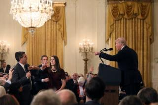 A White House staff member reaches for the microphone held by CNN's Jim Acosta as he questions US President Donald Trump during a news conference following Tuesday's mid-term US congressional elections at the White House, 7 November 2018.