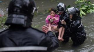 Police officers rescue a child from a flooded street in Hong Kong