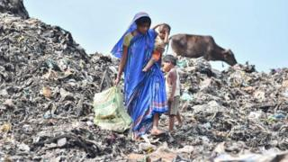 A woman carries her child as she collects firewood at a waste site in India