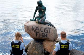 Police take a photo of a statue of a mermaid with the words Racist Fish daubed on it