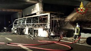 Bombero lanza agua al autobús que se incendió en Verona, Italia.