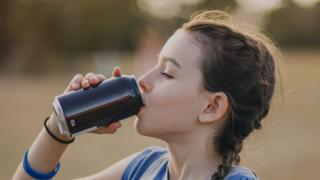 Girl drinking from can