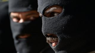Taliban militants wearing balaclavas at a police headquarters in Jalalabad in March