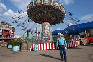 A man in a cowboy hat stands in front of a fair ride
