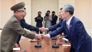 South Korean presidential security adviser Kim Kwan-Jin (right), shakes hands with Hwang Pyong-So (left), North Korea' top political officer for the Korean People's Army. Both are accompanied by another official each, and media.