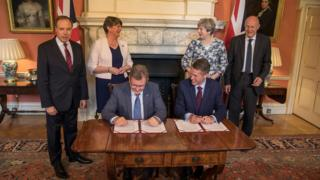 Theresa May and Conservative Party colleagues with Arlene Foster and DUP colleagues at the signing of the deal between the parties