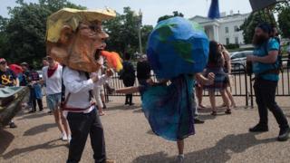 Protesters wearing a mask of US President Donald Trump and one of the Earth pretend to fight in front of the White House during the People's Climate March in Washington, DC, on April 29, 2017