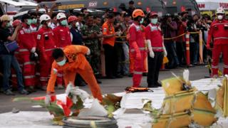 Workers look at parts of the wreckage of crashed Lion Air flight JT610