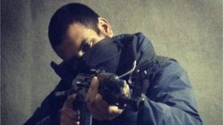 Junaid Hussain holding a gun