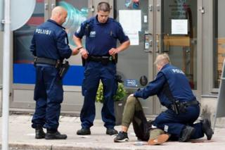 Three armed Finnish police officers tend to a man lying on the pavement at the scene