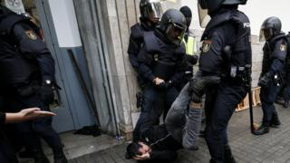 Spanish police drag a man away from a polling station in Catalonia