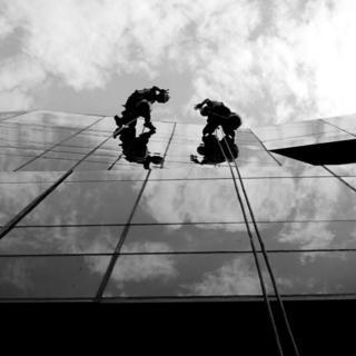 Dos hombres limpiando las ventanas de un edificio