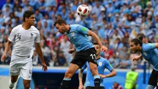 Pemain belakang Prancis, Raphael Varane (kiri) mencetak gol pertama, melampaui penyerang Uruguay, Cristhian Stuani (tengah) dan Martin Caceres.
