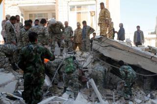 Soldados em torno de escombros
