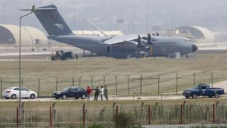 Turkish and US soldiers, with a Turkish Air Force A400M tactical transport aircraft in the background, conduct inspections inside Incirlik airbase