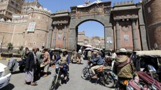 Yemenis walk and ride mopeds through the main gate of the old city ahead of a UN-announced ceasefire, in the old city of Sanaa