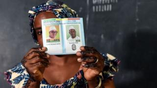 An election official holds a ballot paper at a polling station on 12 August 2018 in Bamako