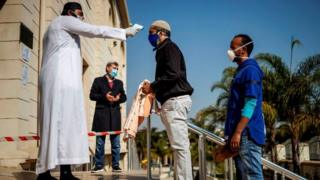 A man carrying a prayer mat and wearing a mask as preventive measure against COVID-19 coronavirus has his temperature checked at the entrance of the Nizamiye Mosque ahead of the Friday prayer in Midrand, Johannesburg, on June 5, 2020