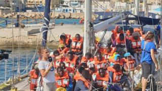 Migrants wearing high-viz lifejackets are seen on the deck of a ship docked in port