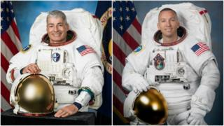 Two astronauts in space suits sit by the USA flag.