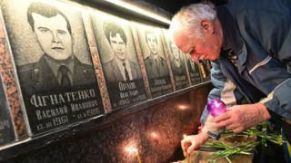 一位老人在切爾諾貝利核事故受害者像前點燃蠟燭