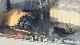 "A yellow sheet covers a U.S. Army helicopter U-60 that crashed on the Navy cargo vessel USNS Red Cloud in the waters around 20 miles (30 kilometers) east of Japan""s southern island of Okinawa Wednesday, Aug. 12, 2015"