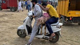 Seorang warga di kawasan bergolak Kashmir, India membawa kambing kurban dari pasar hewan.