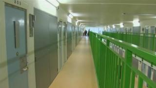 HMP Berwyn prison wing showing a long corridor with closed cell doors