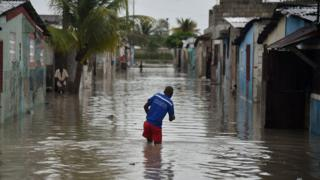 Port-au-Prince şəhərində kişi suyun içi ilə gəzməyə çalışır