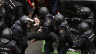 Spanish National riot police evict a young woman during clashes between the people gathered outside the Ramon Llull school and police forces in Barcelona, Catalonia, on 01 October 2017.
