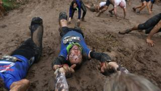 Tel Aviv, Israel, 29 March: One of the 6,000 participants in the Tel Aviv Mud Run in Yarkon Park is helped over an obstacle by a fellow runner.