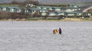 Members of the lifeboat crew wade out to a woman and her dog caught in the tide