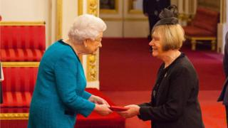 The Queen handing over a medal to Doreen Kenny