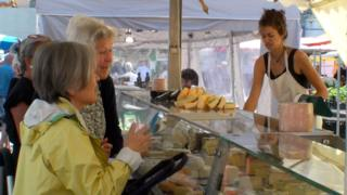 A busy cheese stall at a farmers' market is perused by several ladies