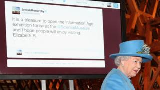 Queen alongside screen showing tweet