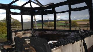 Burnt-down conservatory overlooking Shropshire countryside