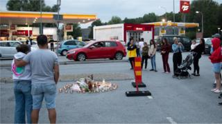 People lay candles and flowers at the site where a twelve year old girl was shot near a petrol station in Botkyrka, south of Stockholm, Sweden, 03 August 2020.