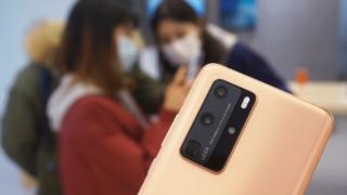 הלוח האחורי של טלפון Huawei P40 נראה בפוקוס חד, על רקע סצנת רקע מטושטשת של לקוחות המנסים את הטלפונים