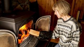 Woman putting log in stove